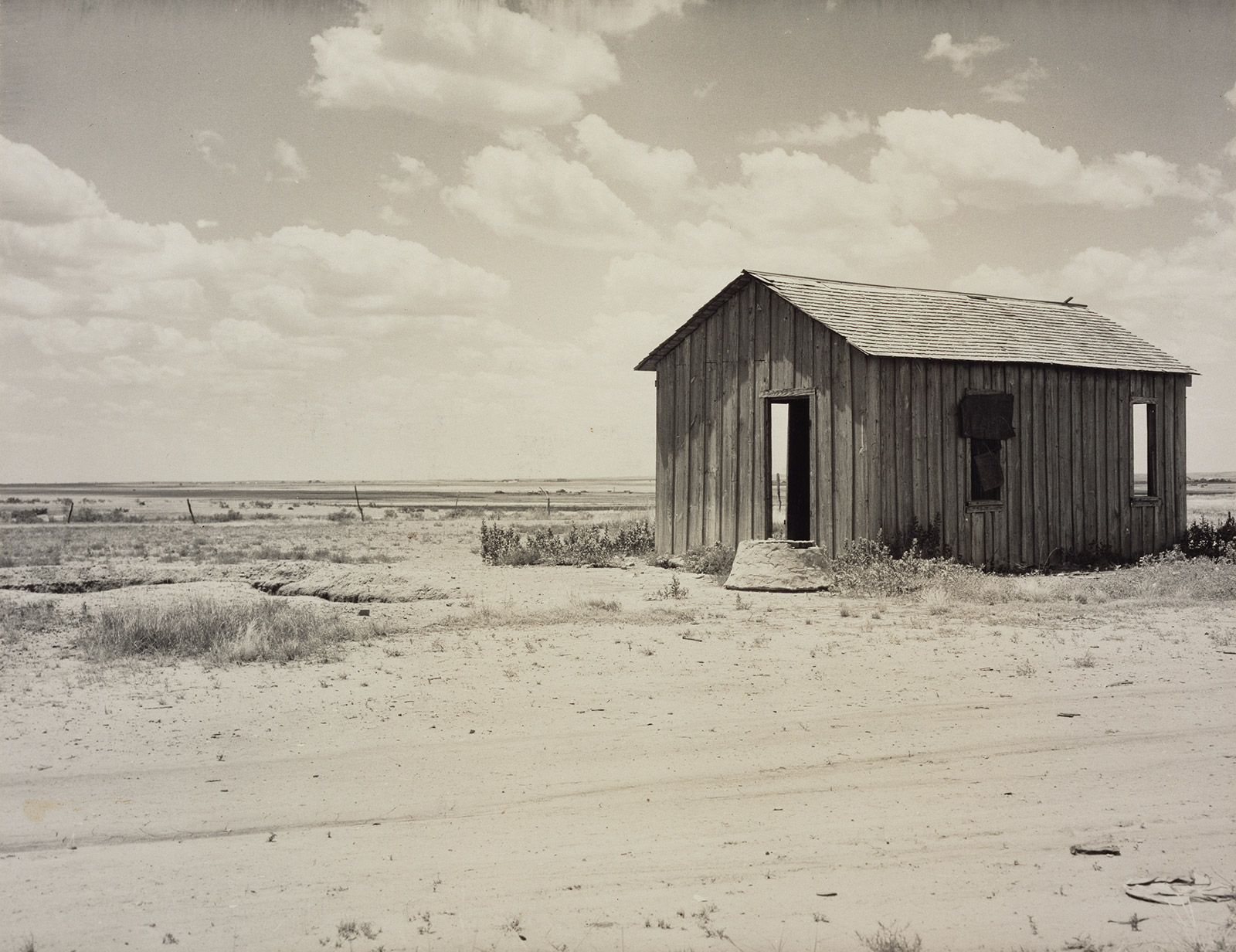 Small abandoned shack with one door and two windows visible, on a barren plain with nothing in the distance.