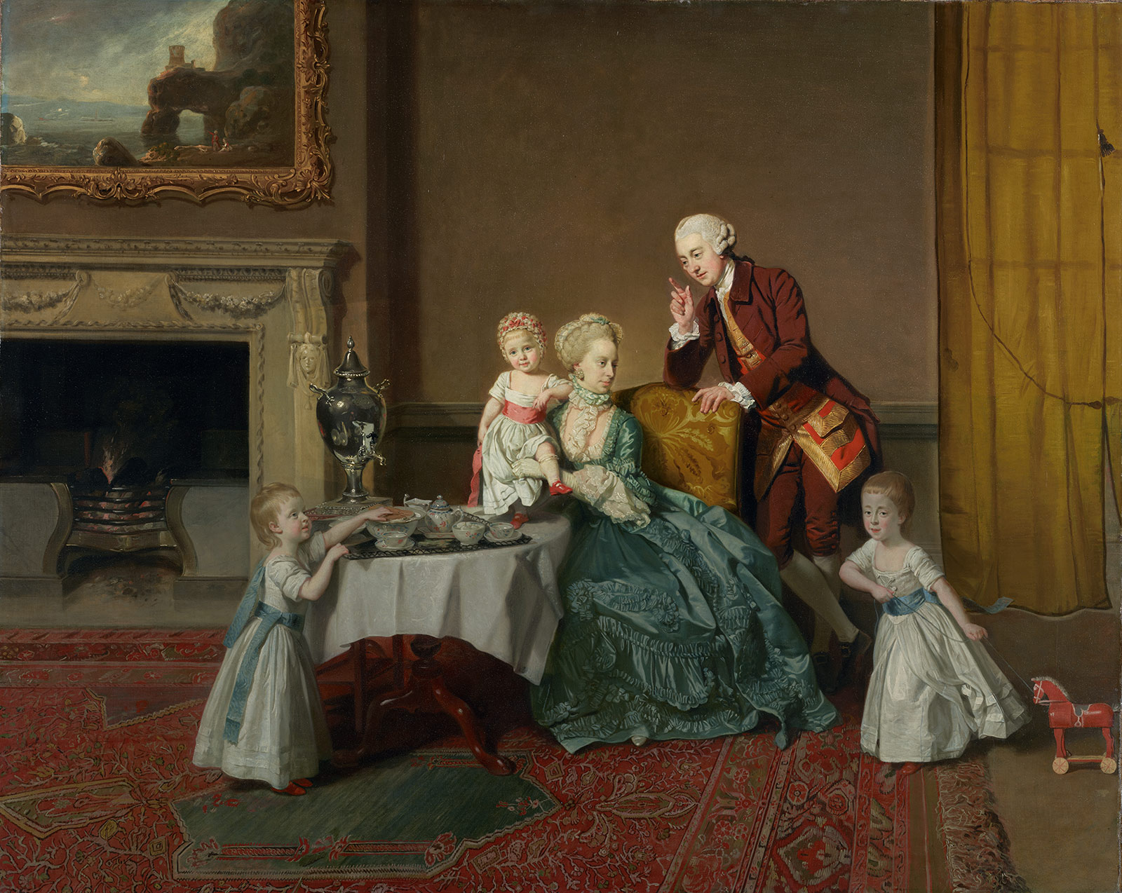 A woman in a blue-green dress sits in a chair, holding a young girl, behind a small table set for tea. Two more small girls stand, one reaching for something on the table, the other pulling a small toy horse. A man in a red waistcoat leans on the chair behind them all.