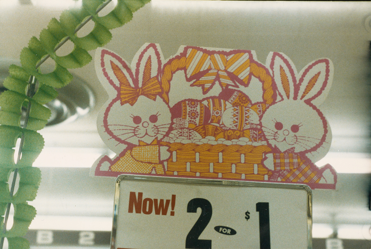 An in-store sign for 2 for $1, topped by a yellow, pink and white illustration of two bunnies holding an Easter basket