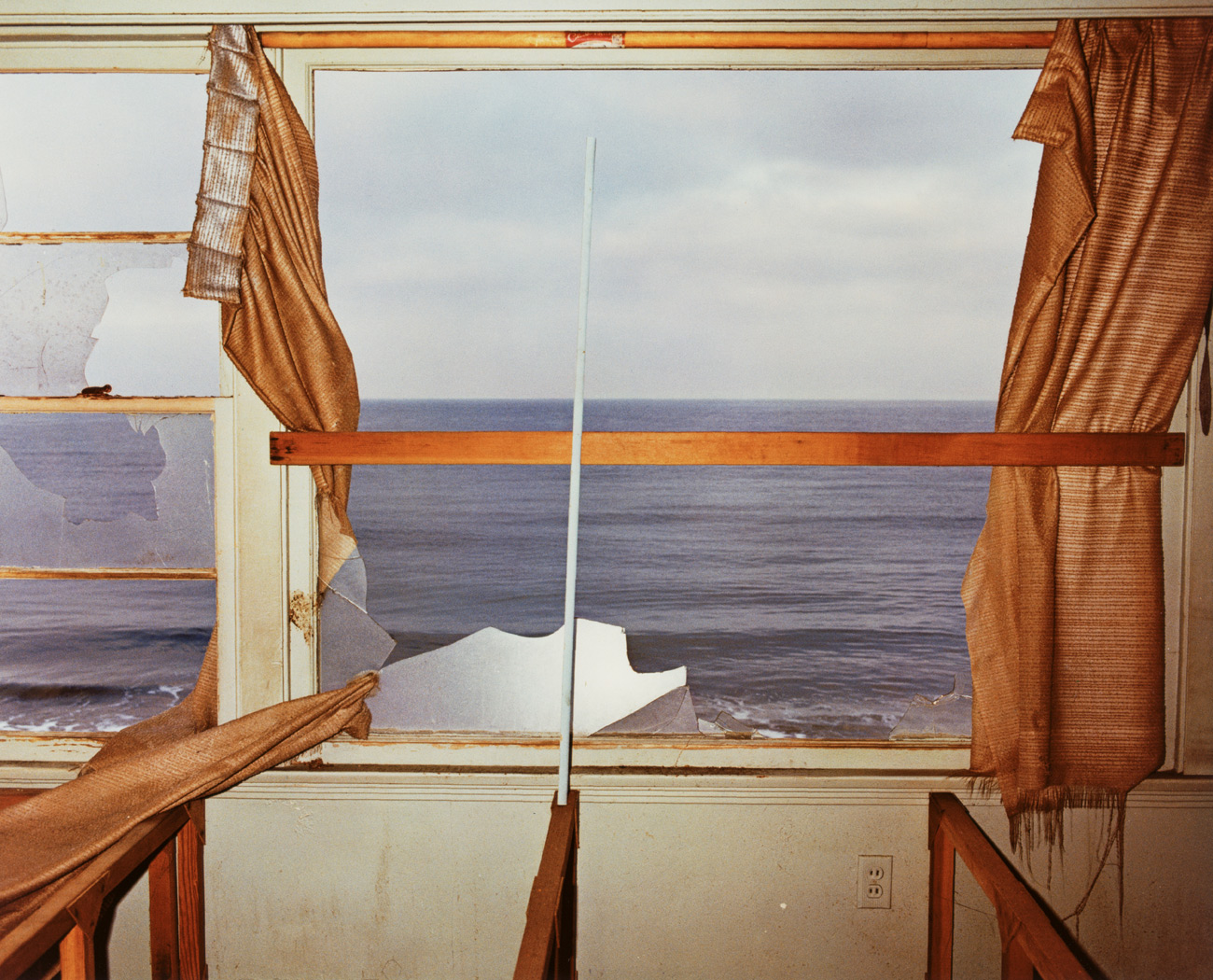 View of the ocean as seen from inside a broken window with tattered curtains falling off the rods.