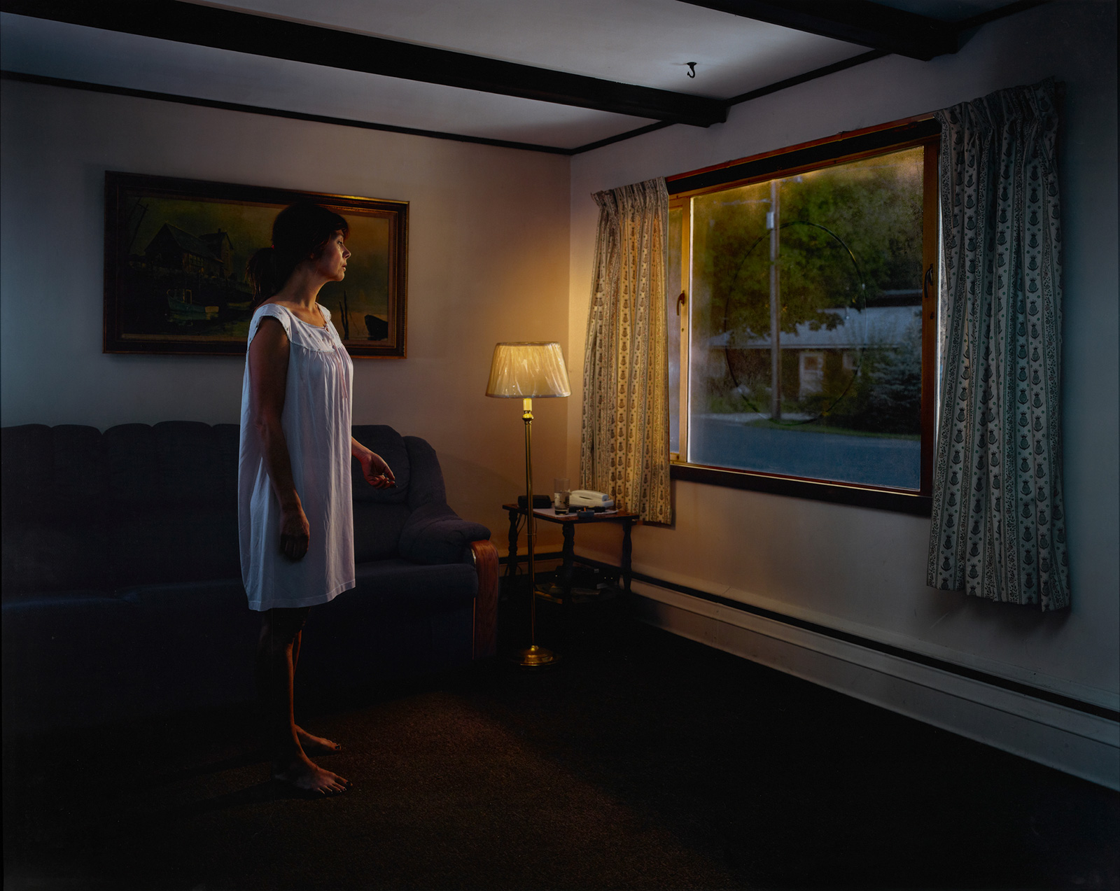 A woman in a nightgown stands in a room with a couch and a lit floor lamp, looking out a large picture window. A house is visible, lit by a streetlamp.