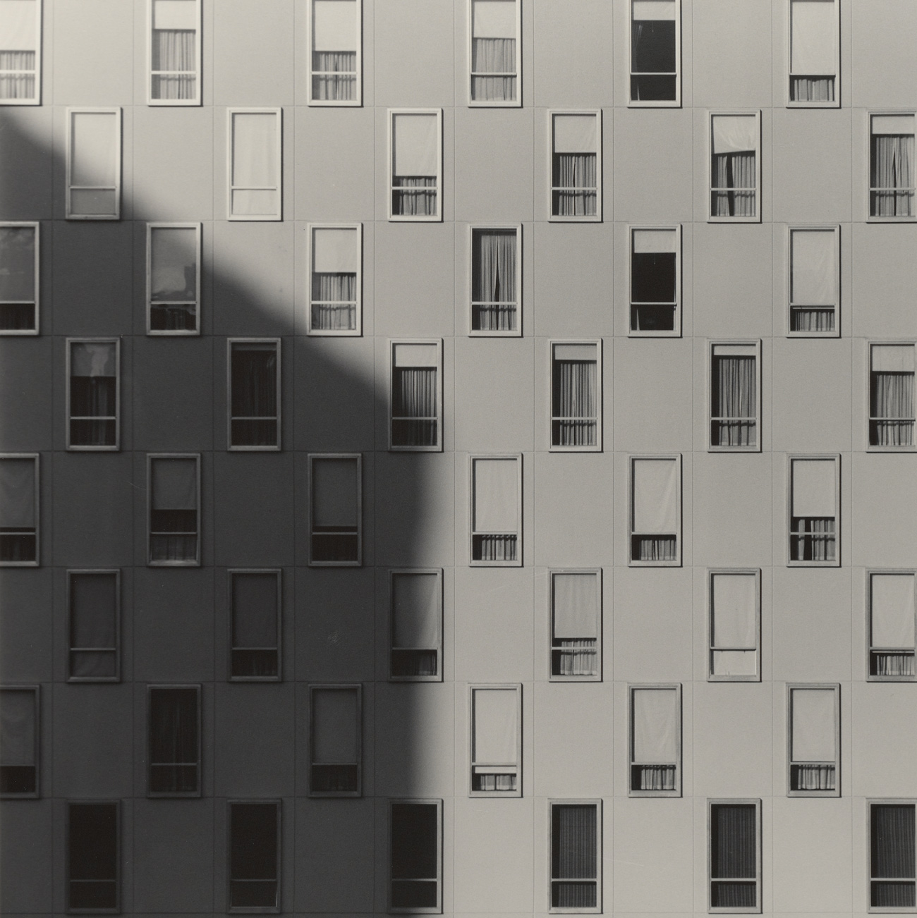 Many windows in a checkerboard pattern, all uniformly sized, some with blinds open, closed, or partially pulled down. A shadow is cast from the left.