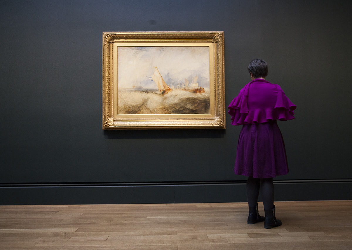 A person in purple stands before a dark wall holding a Turner painting of ships on a rough sea.