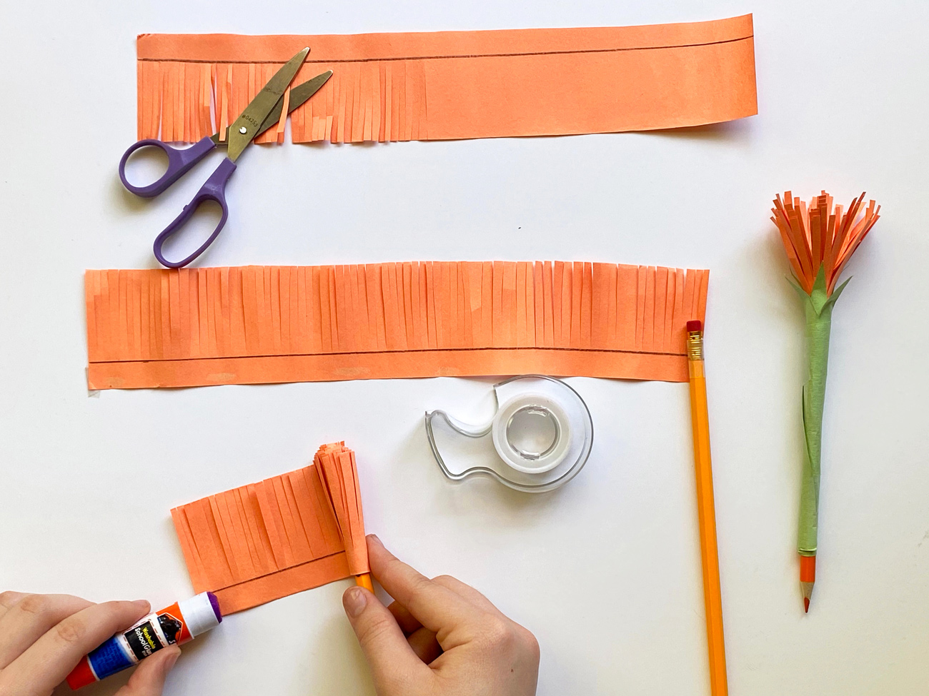 Orange paper cut in strips, rolled around a pencil