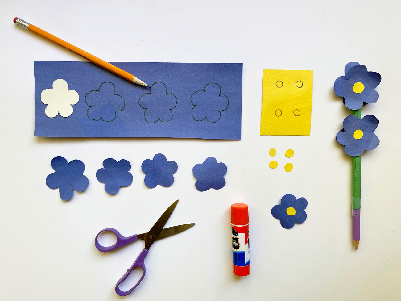 Blue paper with flower shapes drawn on, cut out blue flowers, a paper-wrapped pencil with paper flowers glued on.
