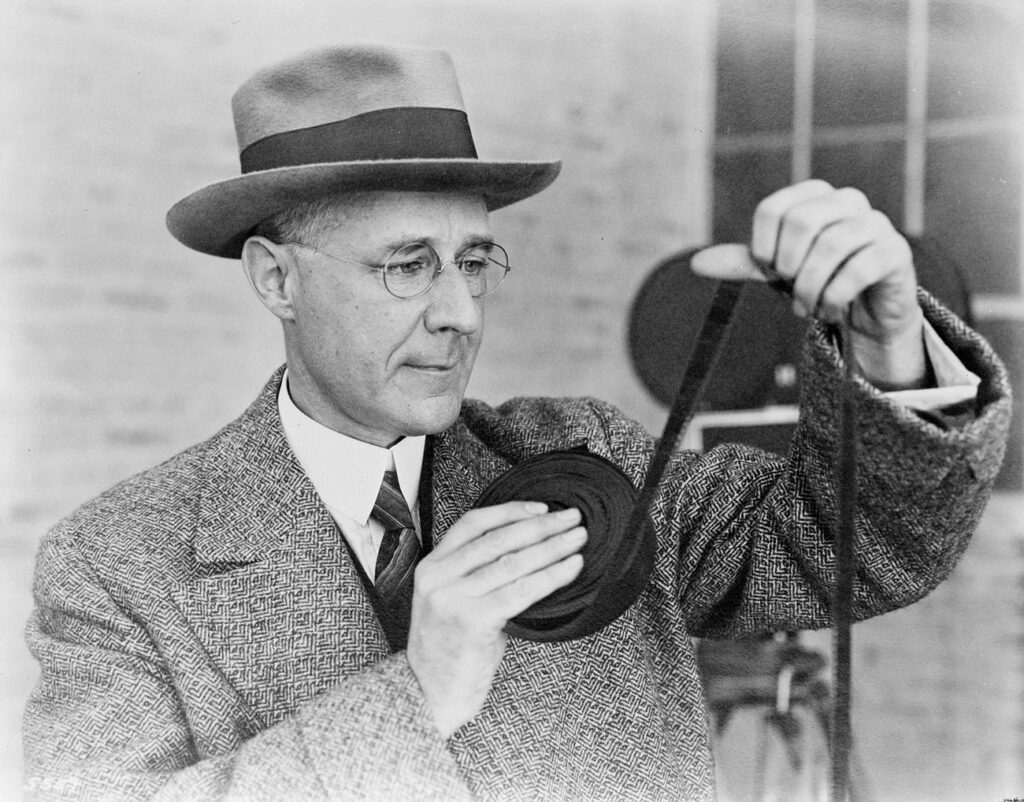 Herbert Kalmus wears a hat, glasses, and a tweed jacket while looking at a roll of film
