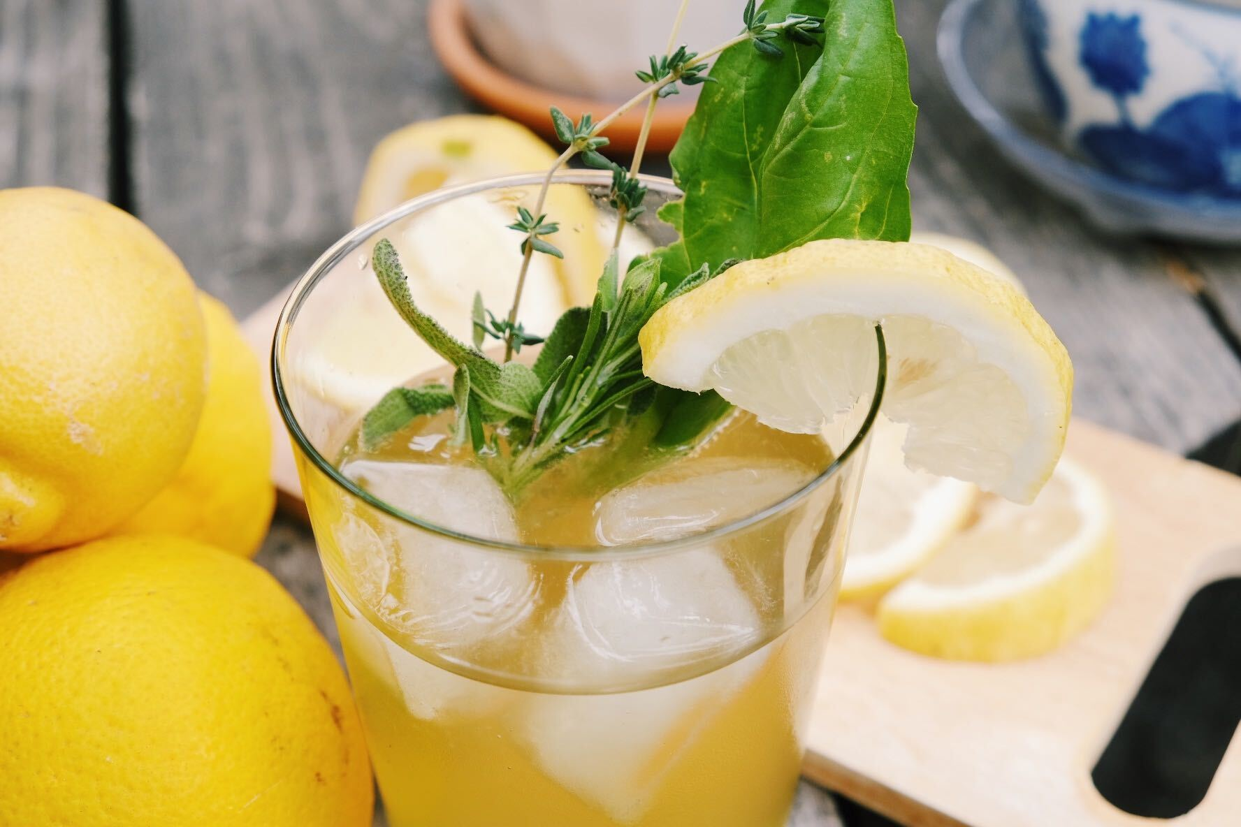 Glass holding ice, yellow lemon juice, and herbs for decoration.