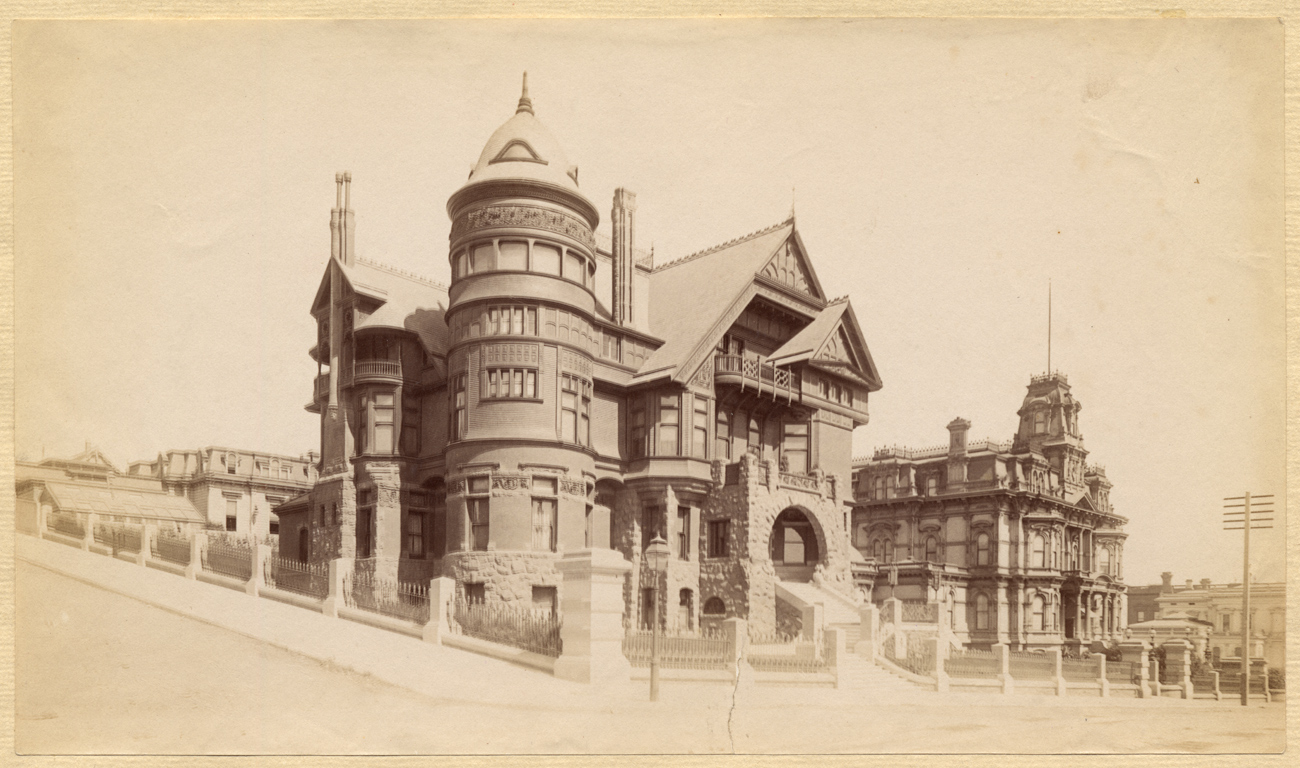 Sepia photo of a large house with gables and turrets, with nothing else nearby
