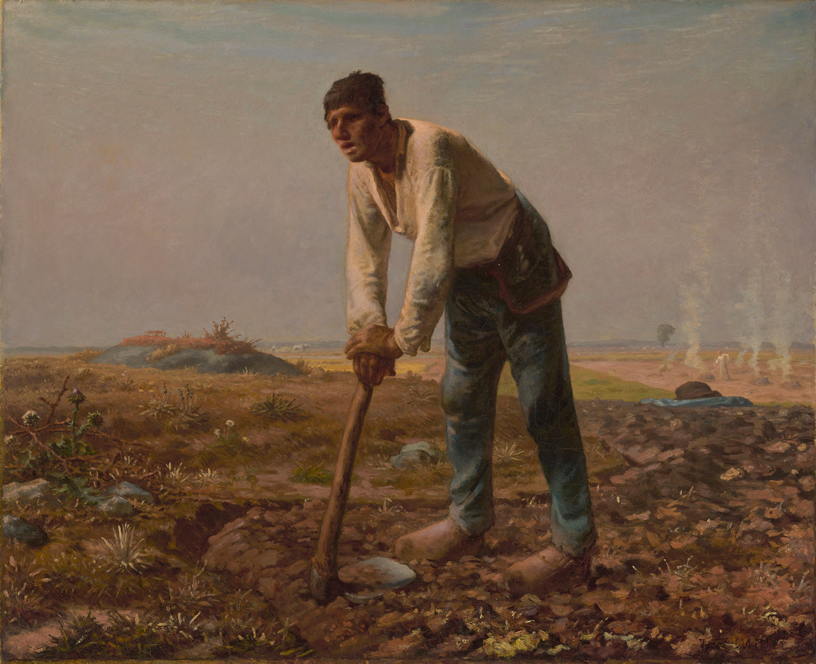 A man in a white shirt and jeans leans on a hoe in a field