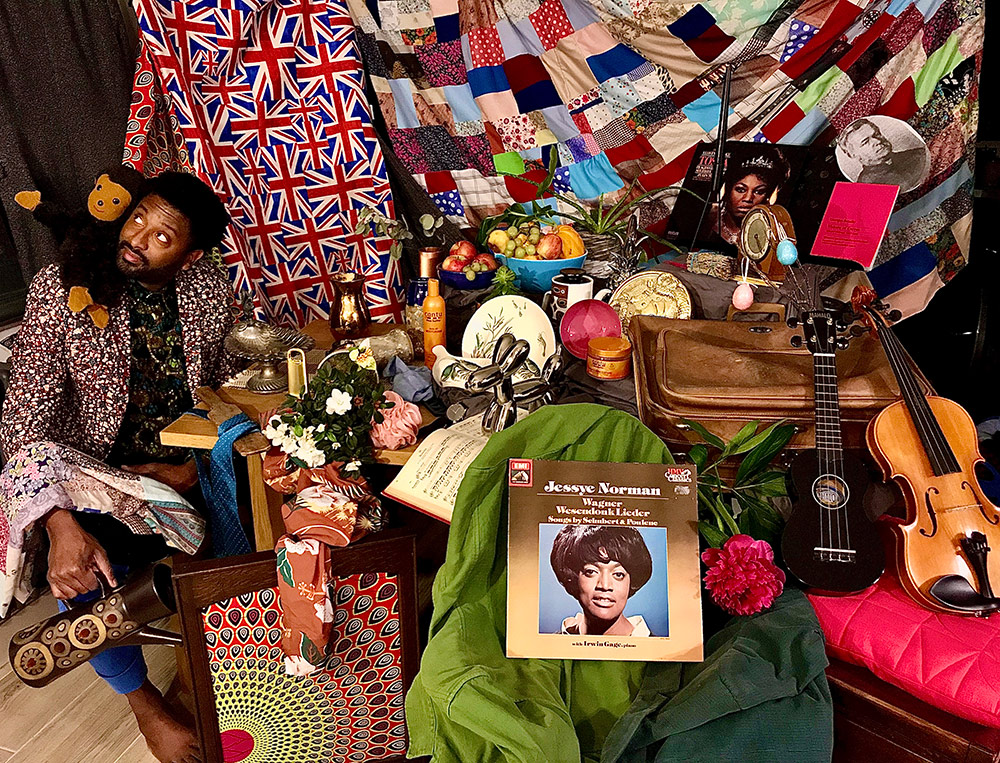 Brathwaite sits with a stuffed Curious George on his shoulder, in a room filled with a lot of stuff, including musical instruments, albums, and fruit. Quilts and blankets hang in the back.