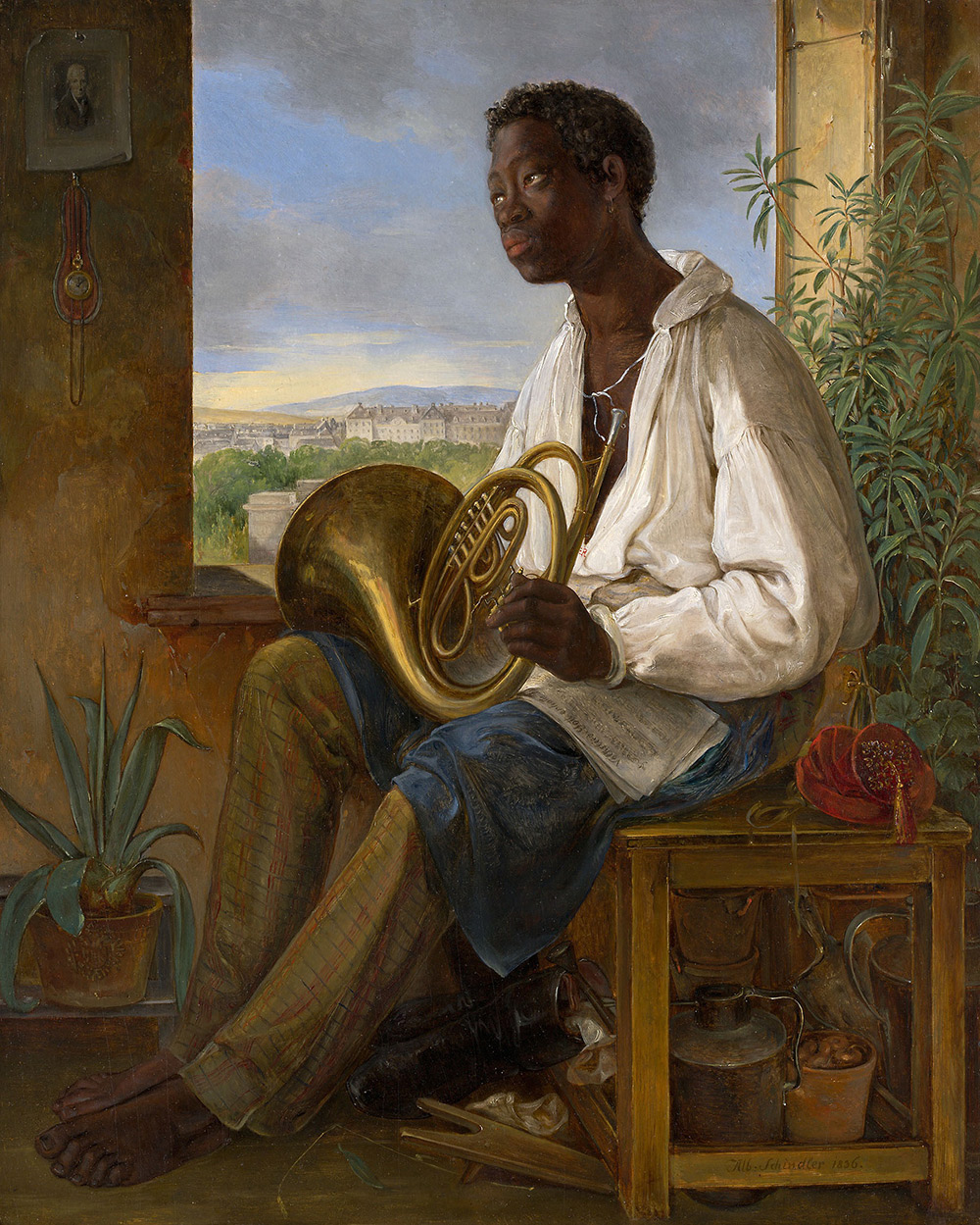 A dark-skinned man (or boy) sits by a window. He's wearing a white shirt and holding a French horn.