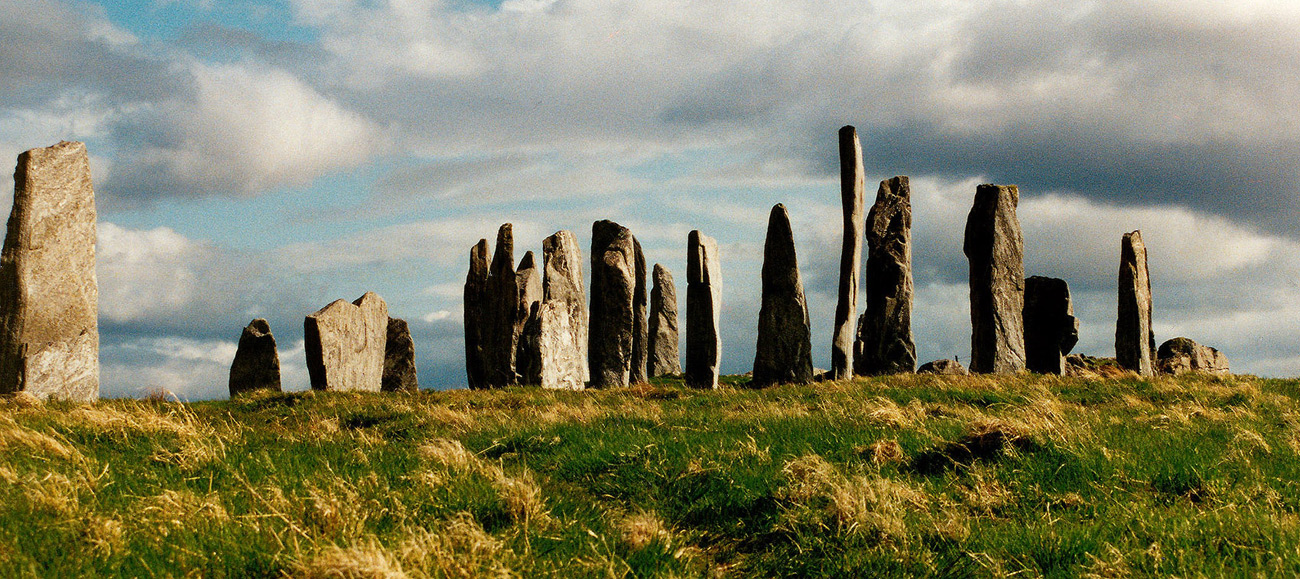An array of henge-like stones, with dark clouds behind
