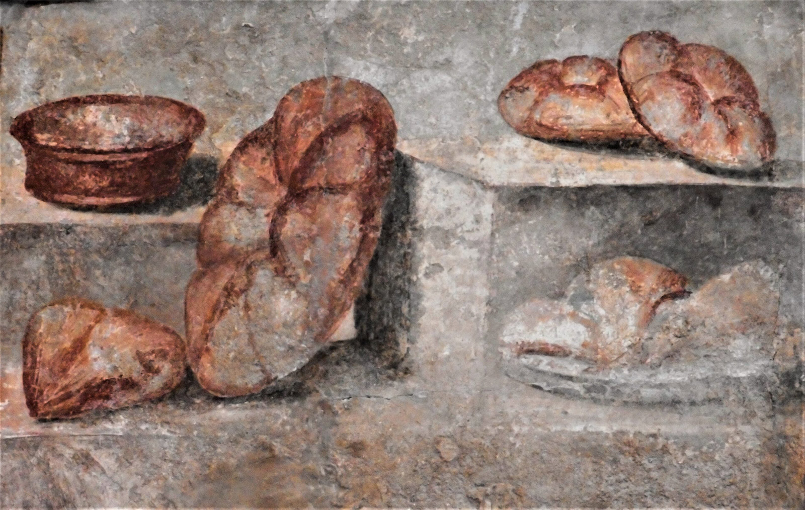 A pastel fresco, with brown round loaves of bread that sit on a shelf