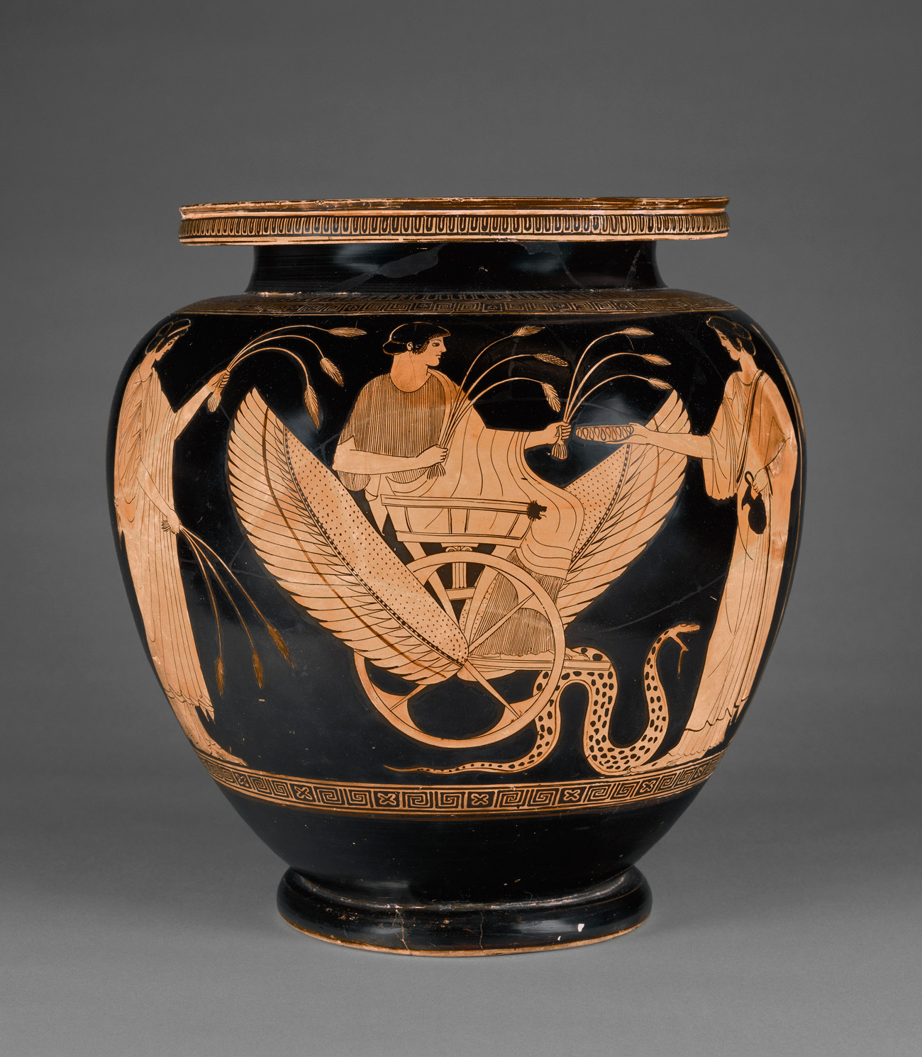 Greek vase with an image of a person sitting in a carriage holding stalks of wheat.