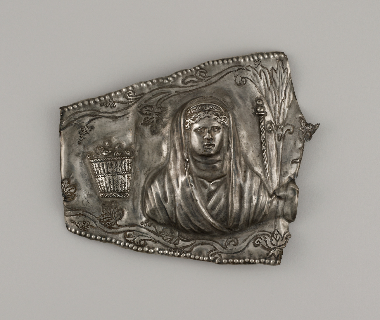 A silver piece with the image of a woman.