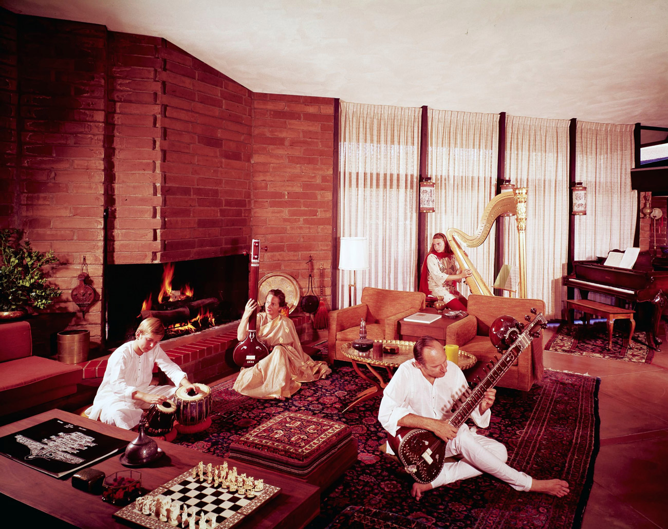 Four musicians with classical instruments, including a large harp, are seated in an expansive living room decorated in shades of red