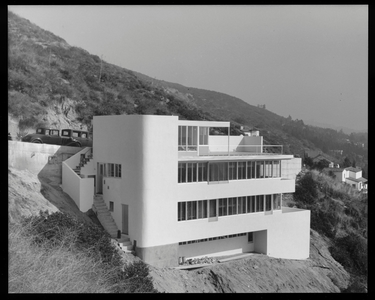 Black and white photo of four story home built into side of cliff overlooking a canyon