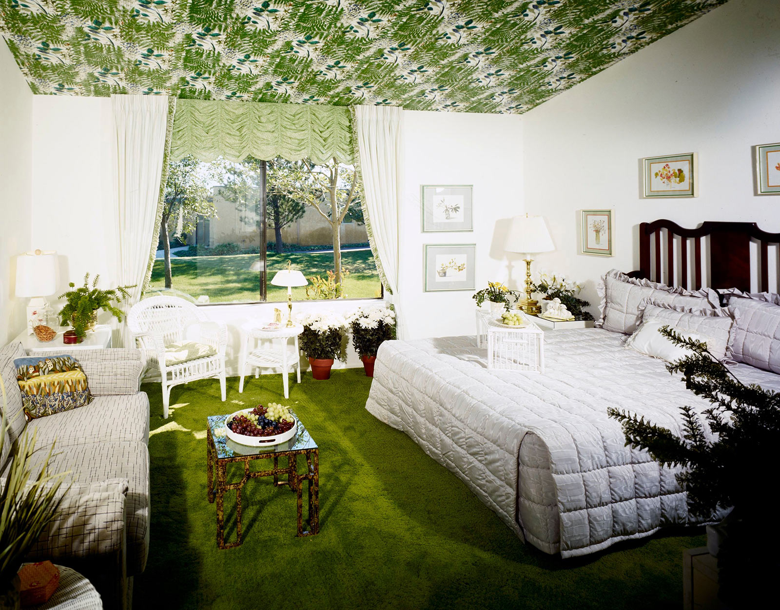 Bedroom with white and gray linens and accents, grass green carpet, and green leaf patterned ceiling