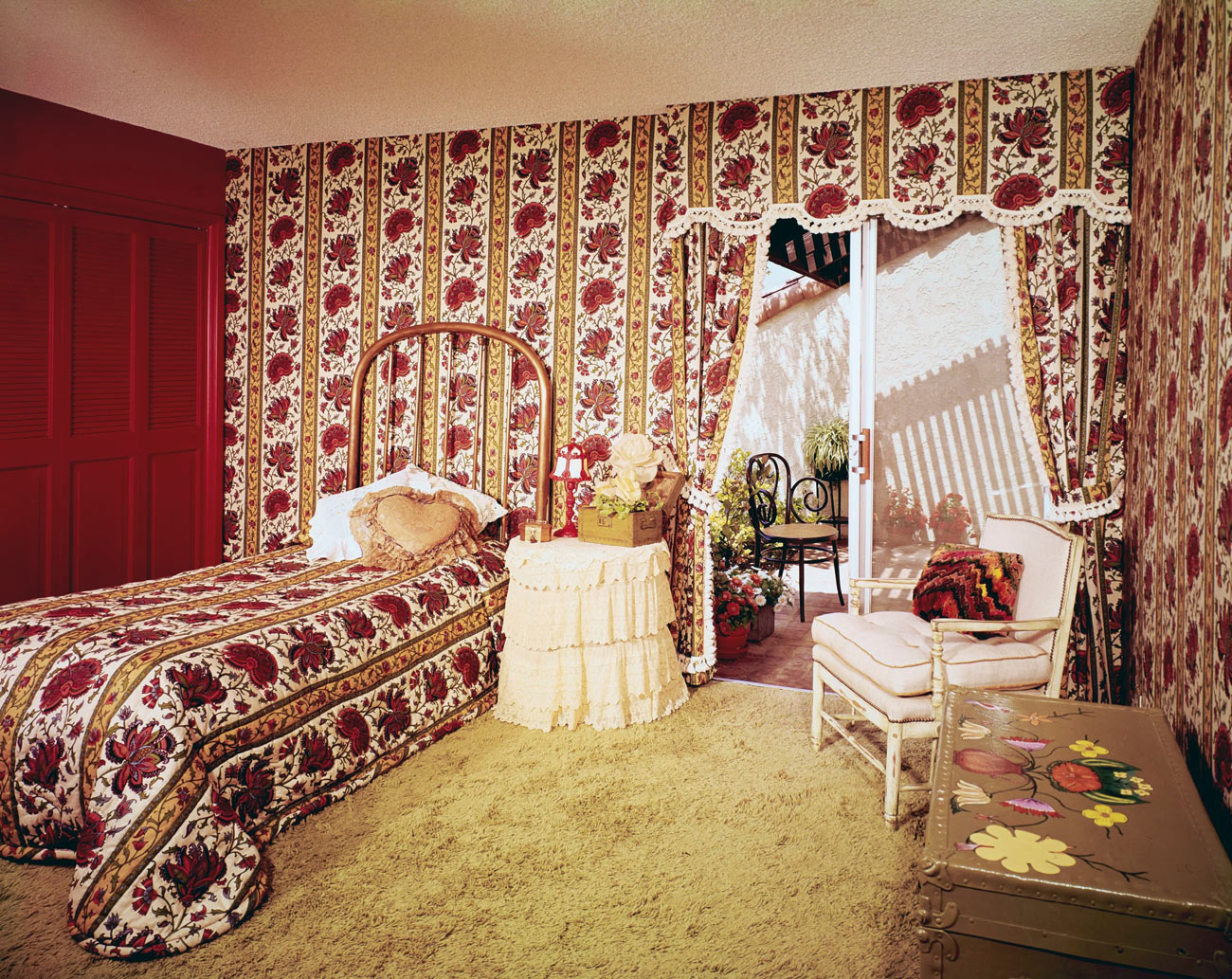 Bedroom with floral and stripe patterned wallpaper and matching bedspread on the twin bed.