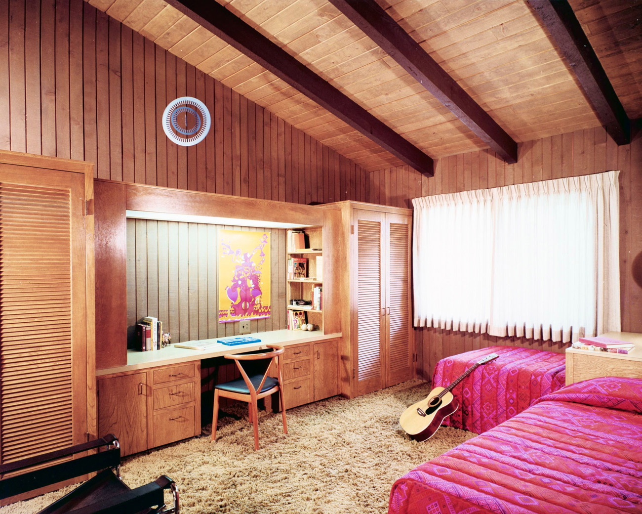 Wood paneled bedroom with slanting wood ceiling, two twin beds with pink linens, a desk and an acoustic guitar