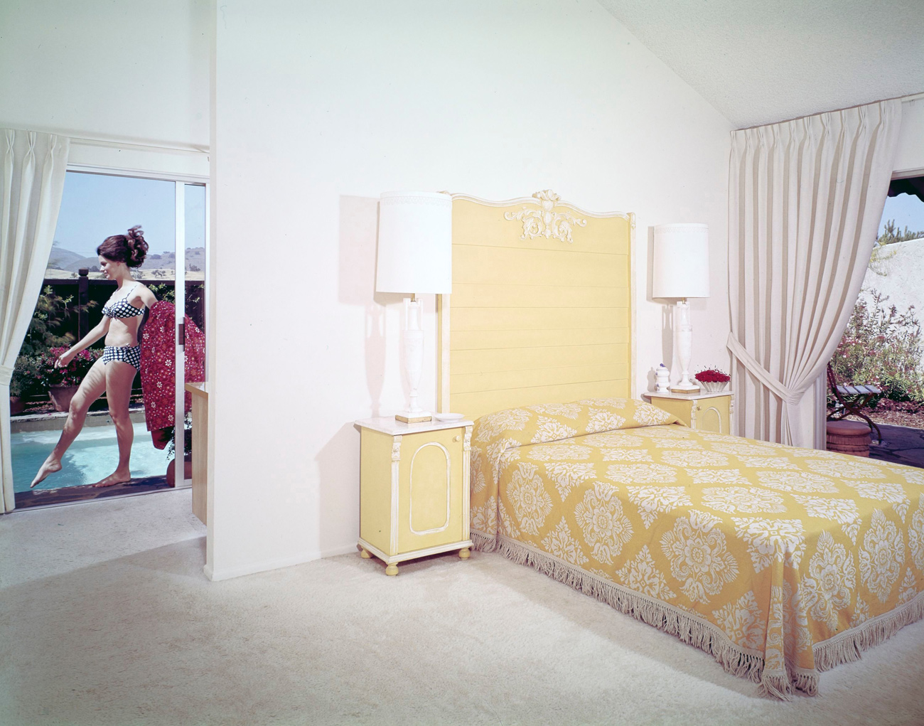 White bedroom with yellow accents. A woman is seen through a window by the pool.