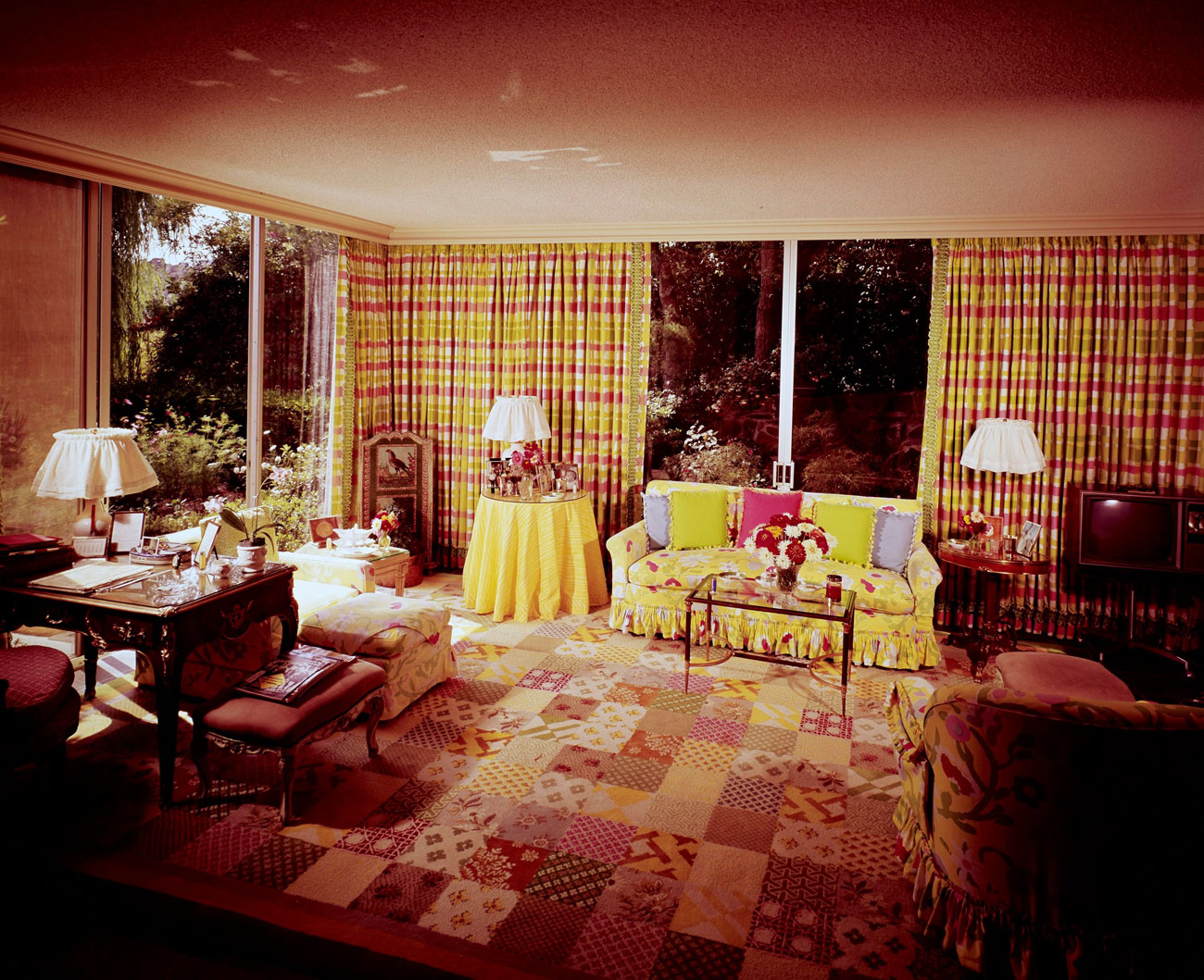 Living room with yellow and red accents. The carpet looks like a patchwork quilt.