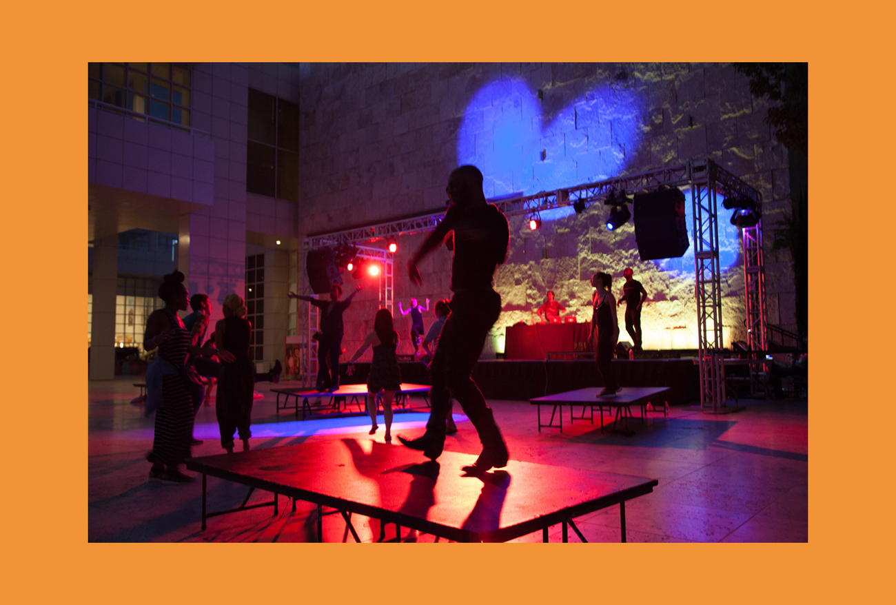 People dance on low platform tables and on a stage in front of a large travertine wall lit with a blue heart shape