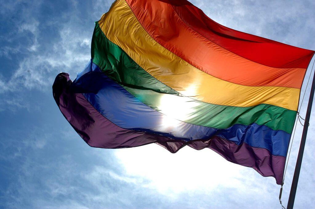 rainbow flag against a blue sky