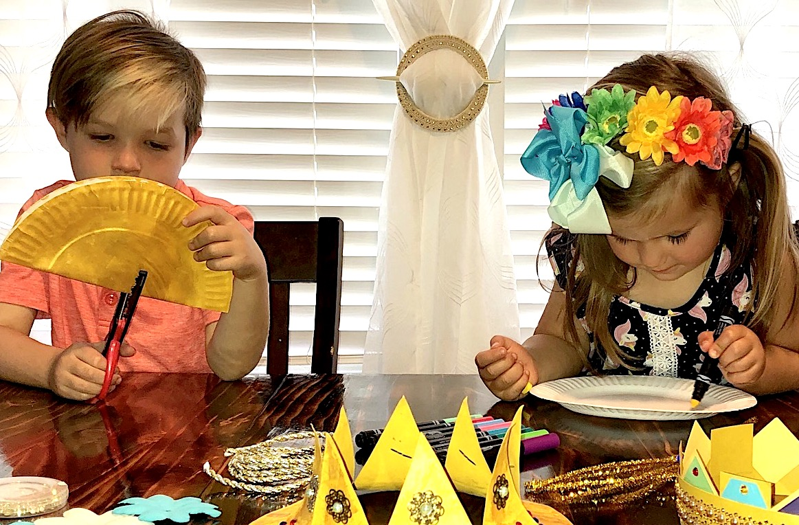 Two children sit at a table making crowns with paper plates