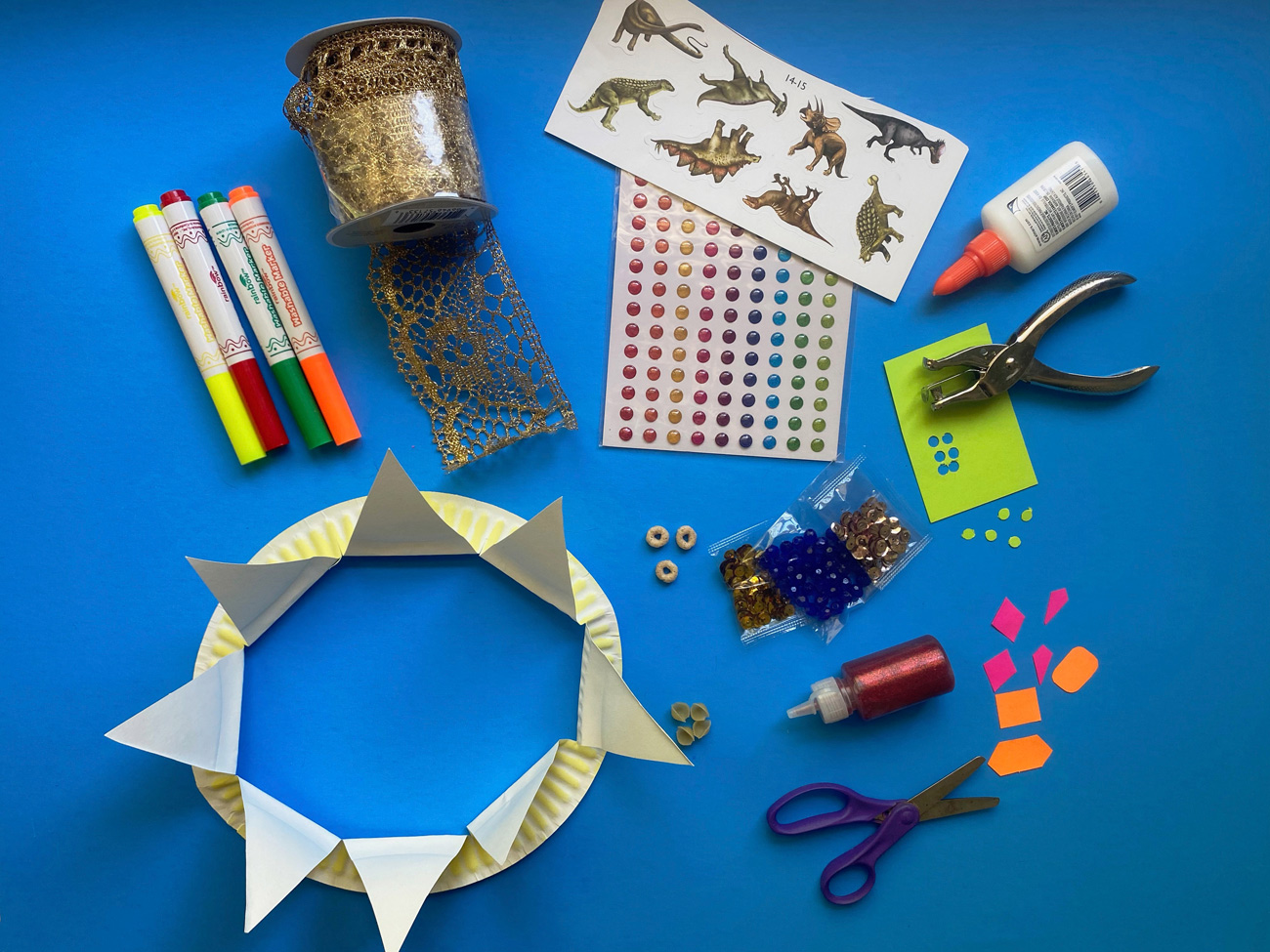 A completed crown sits on a blue surface alongside pens, stickers, and other crafting materials