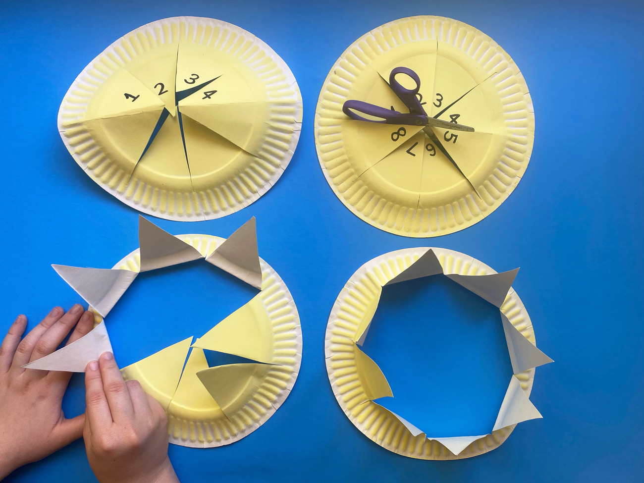 Paper plates with pie-shaped cuts being turned up to form crown points