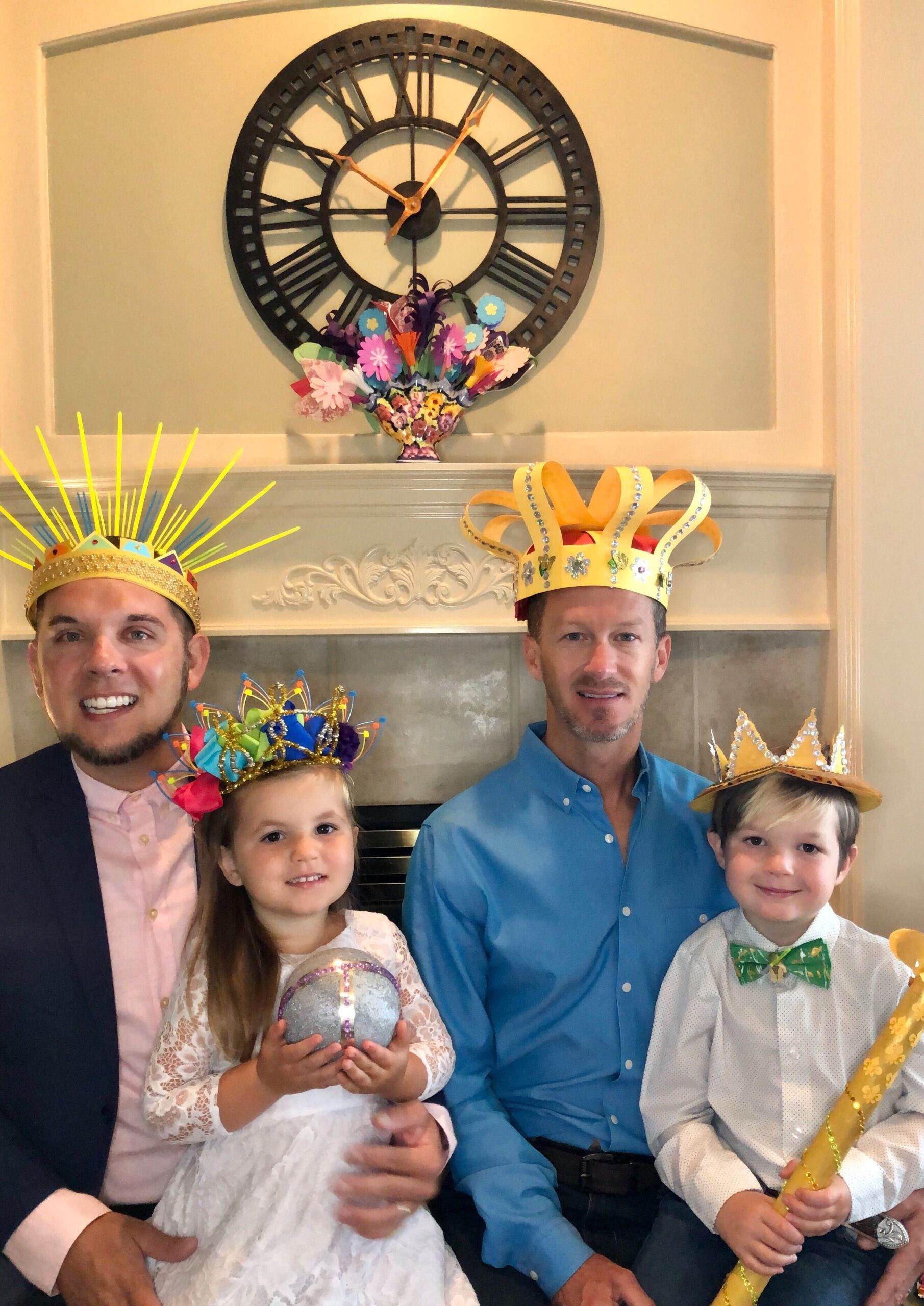 A family of four--two dads, a boy and a girl--all wear crafted crowns