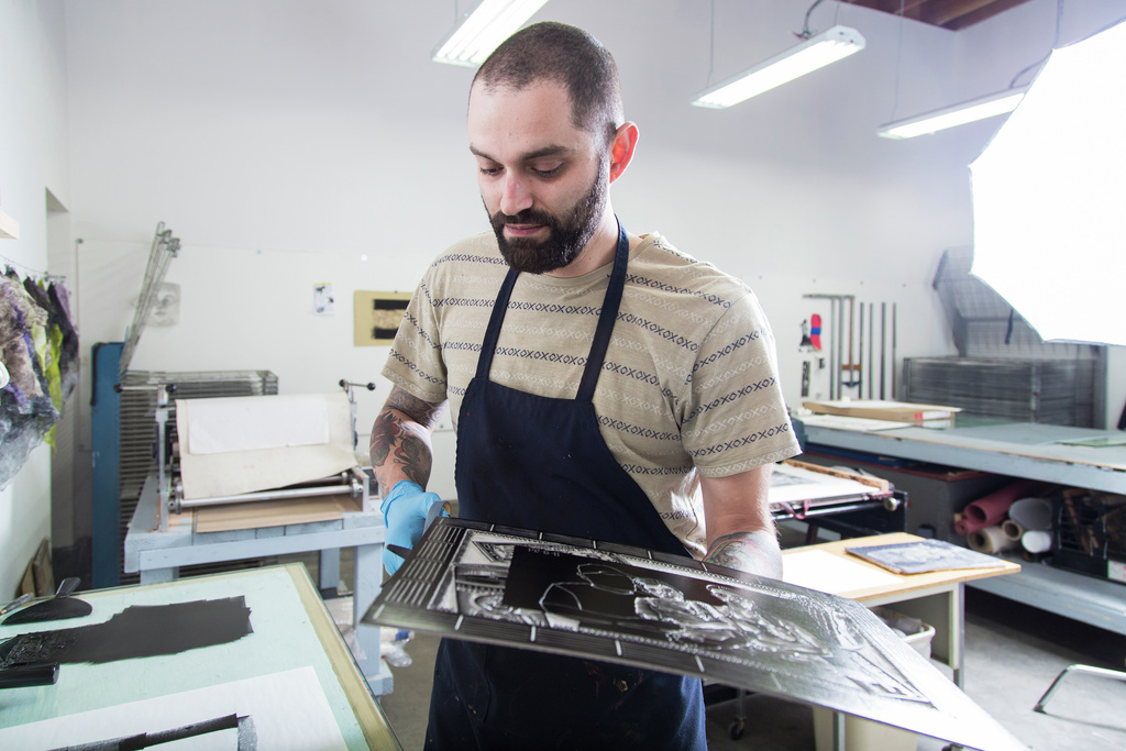 Man in an art studio looks at a black and white piece of paper from a printing press