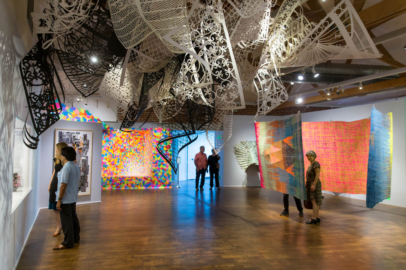 Big gallery space, with six people looking at big multi colored fabric hanging from the ceiling