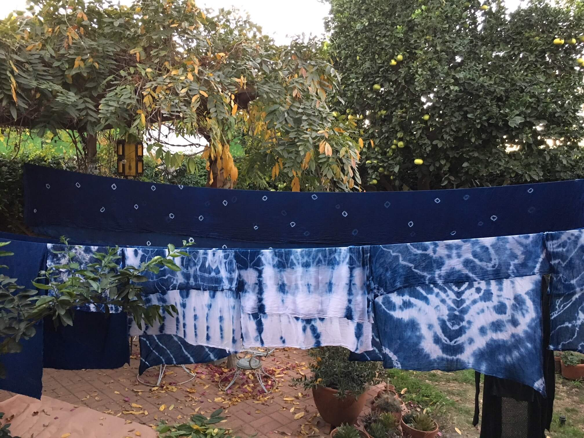 Blue fabric with tie-dyed designs hang outside on a clothesline