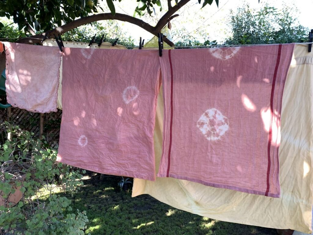 Squares of fabric, mostly pink, hang outside from a clothesline