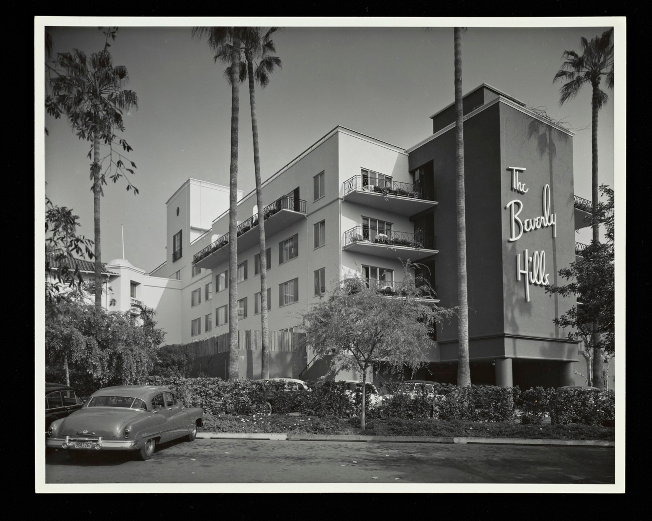 Black and white photo of 4-story building with parking lot in foreground. The words 'The Beverly Hills' appear on the front of the building