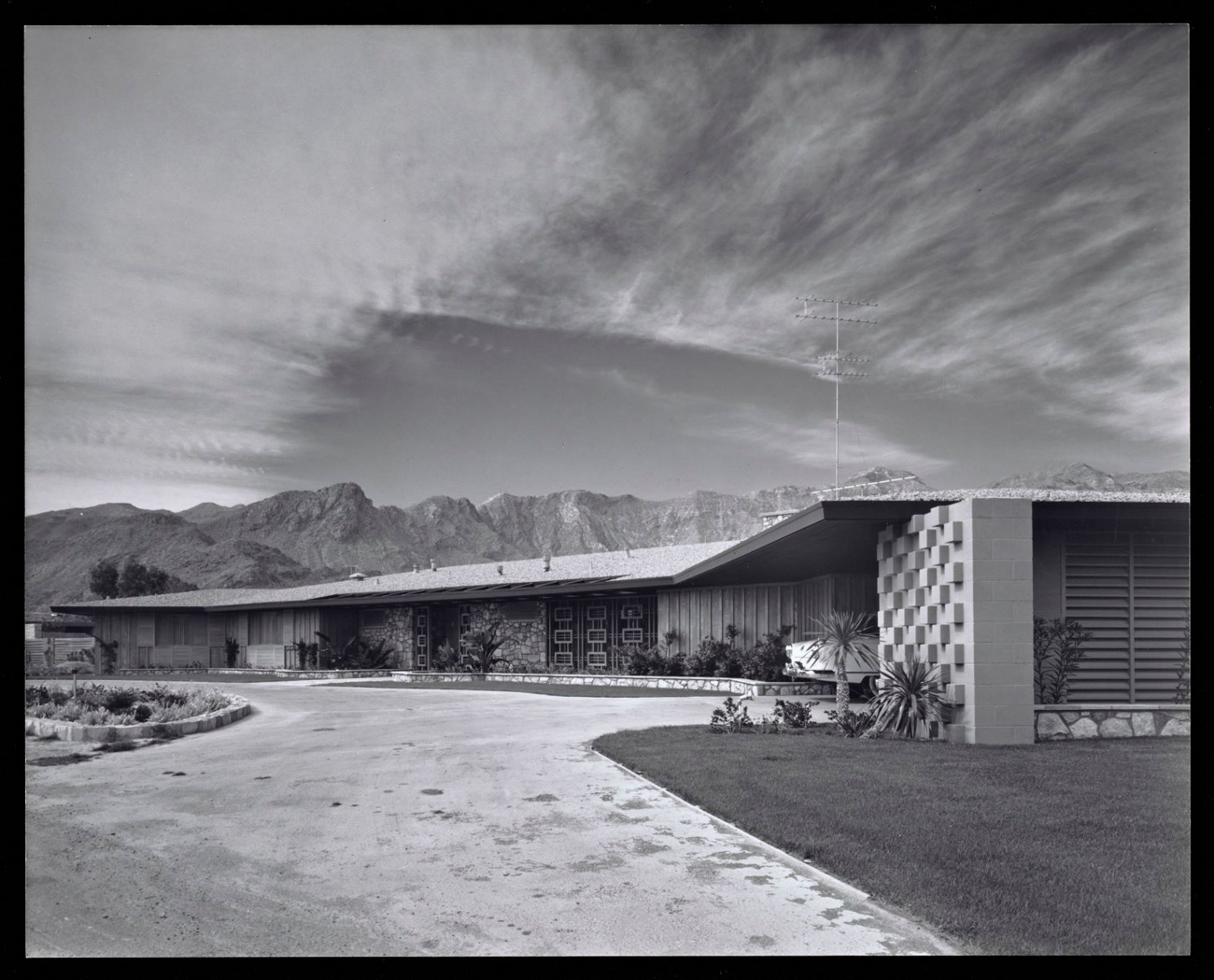 A long, single story ranch house. Driveway in the foreground, mountains and expansive sky in the background.