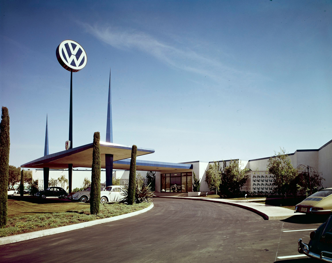 Single-story VW dealership with blue spires and a curving driveway