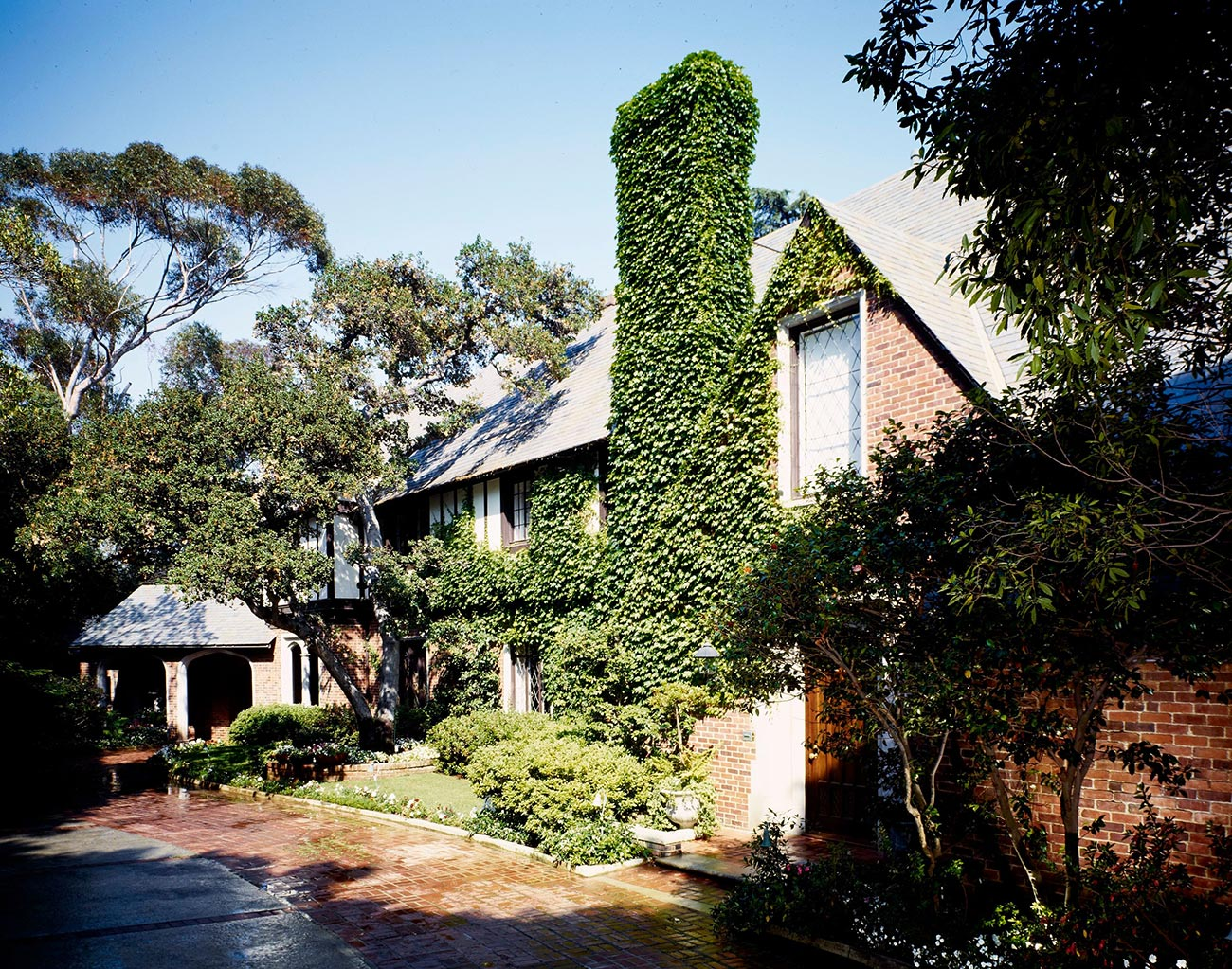 Two story red brick house covered in ivy, with a brick driveway