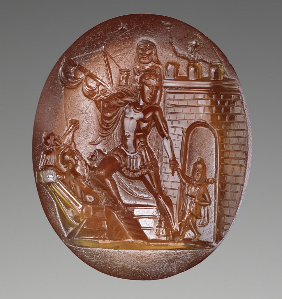 Red-orange gemstone with a carved scene depicting Aeneas (center) with his father on his shoulder and son at his right side. There is a brick wall with an arched entryway behind them and at the bottom left are ships.