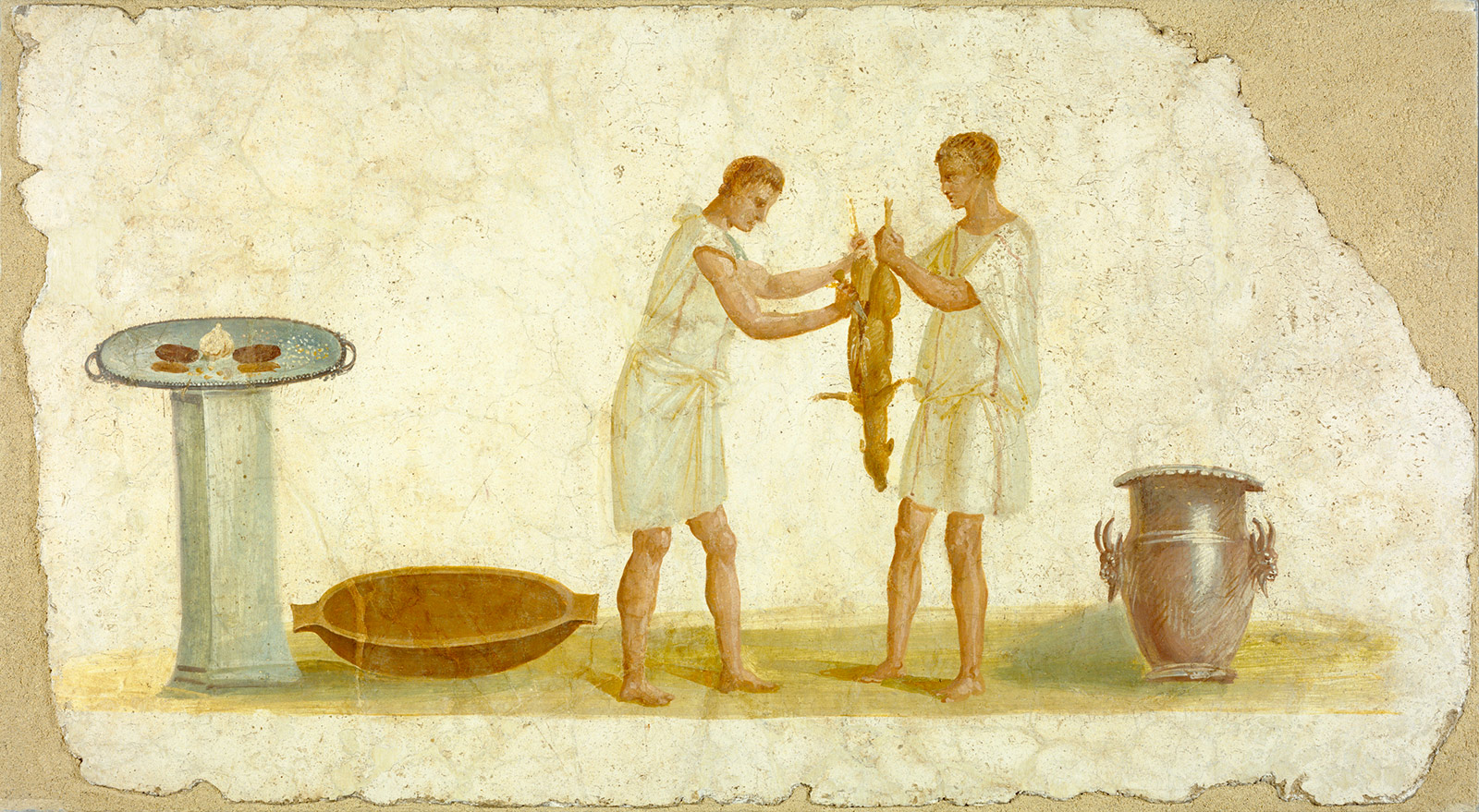 One person holds an animal carcass, possibly a deer, while another uses a knife to cut it down the center. Both wear togas.