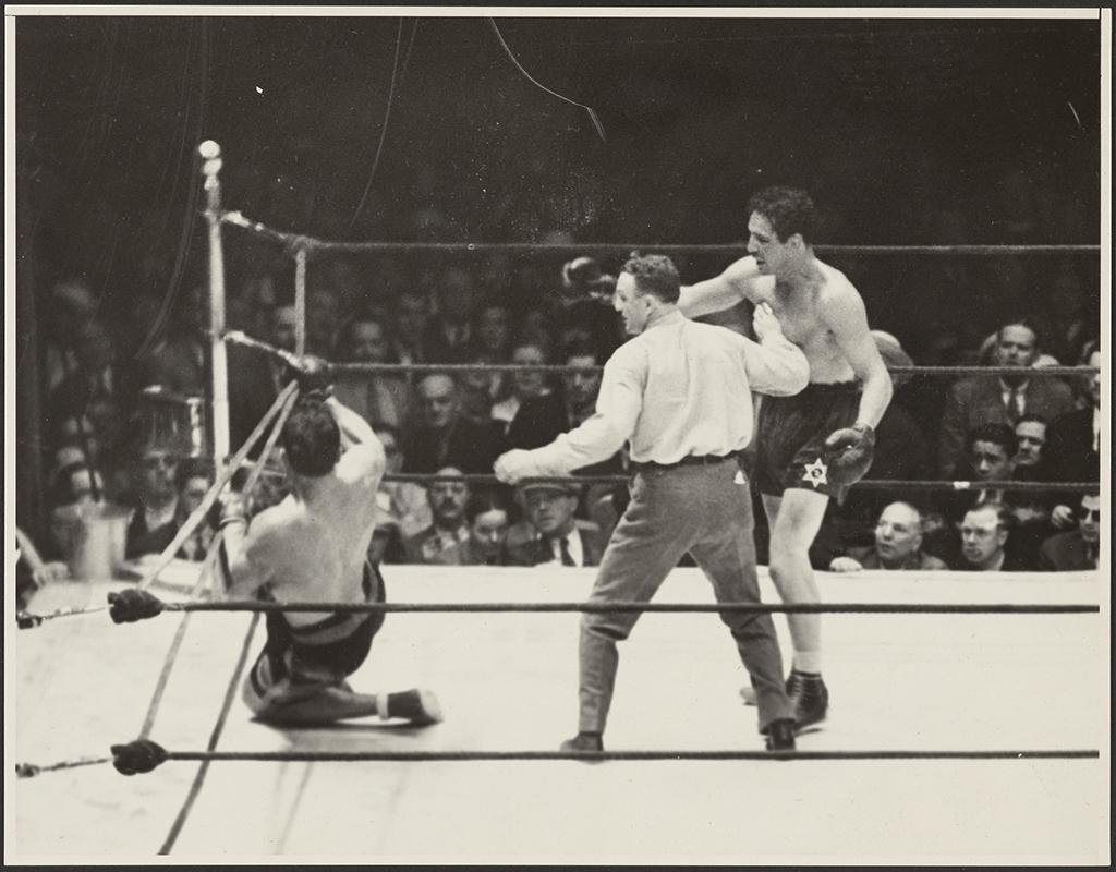 Ref holds Baer back as Carnera hangs on the ropes, left knee on the mat