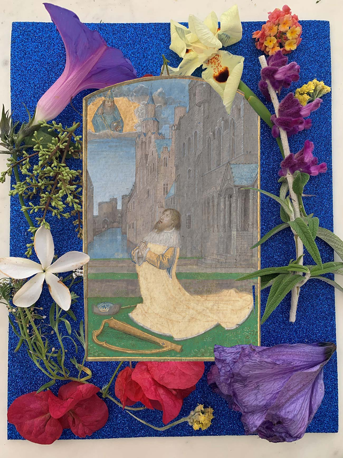 Glittery blue page with picture of man praying in front of a castle in the center, surrounded by real flowers along the outside border