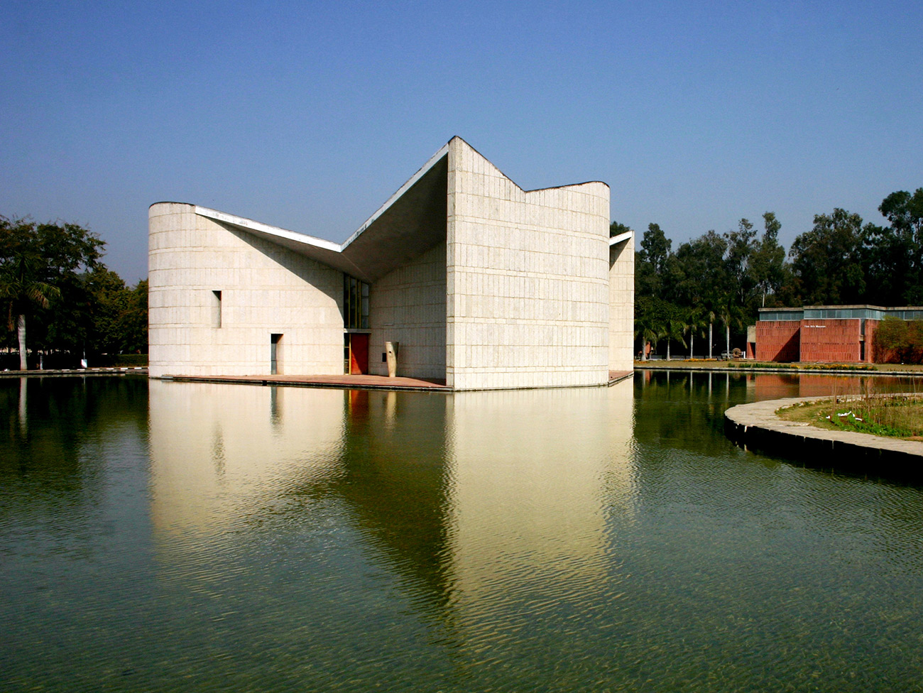 Asymmetrical white cement building that appears to sit directly on a lake