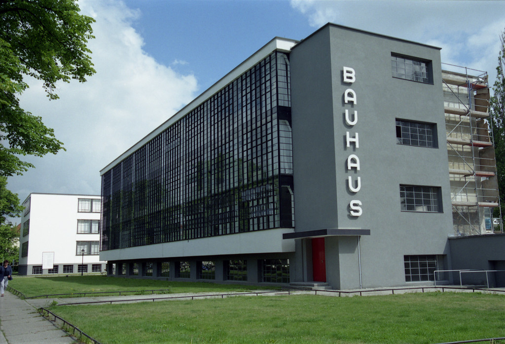 Four story gray building with BAUHAUS displayed vertically on the side in large white letters