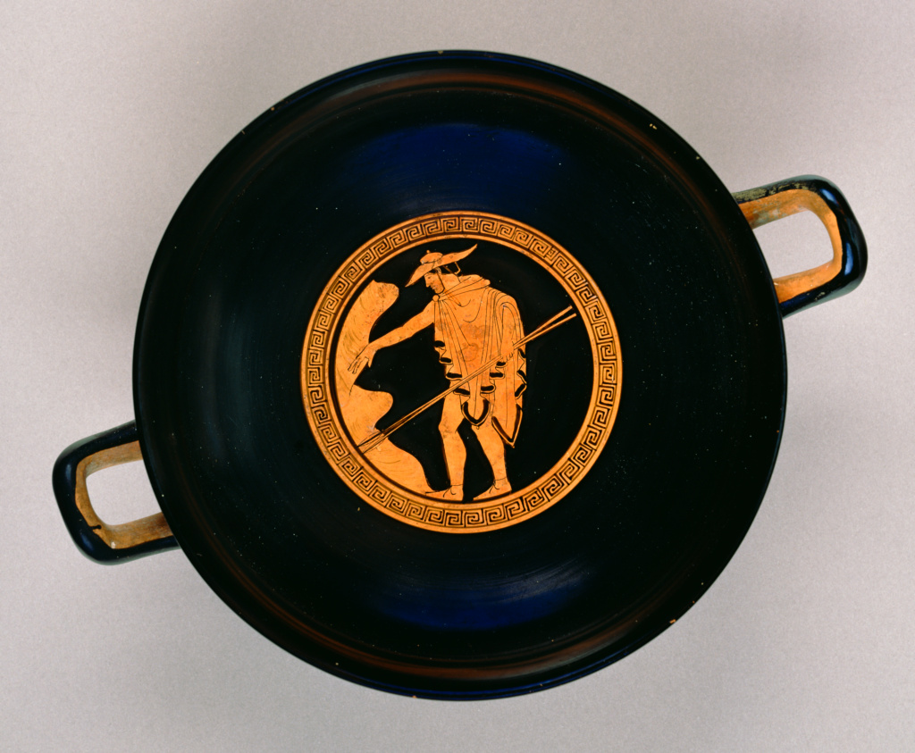 Inside of flat black cup with two handles, showing an orange person wearing a hat and cloak and carrying two staffs in his left hand