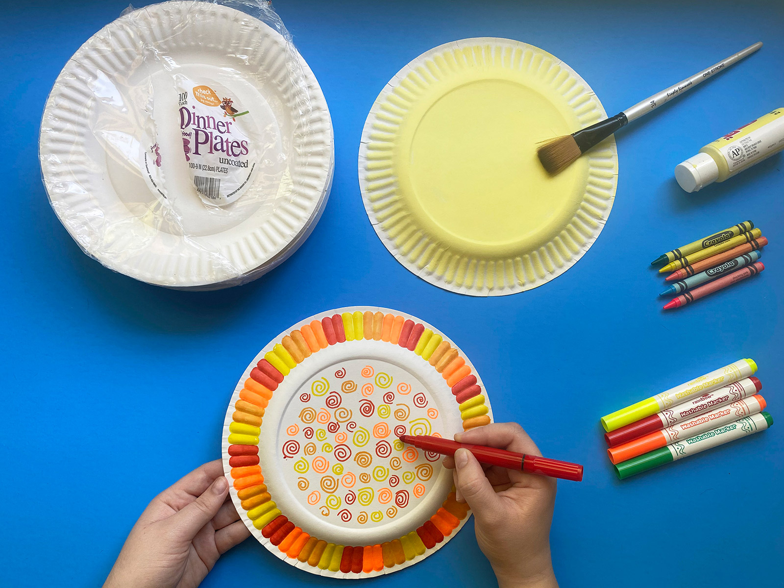 Paper plates being decorated with yellow, orange and red markers