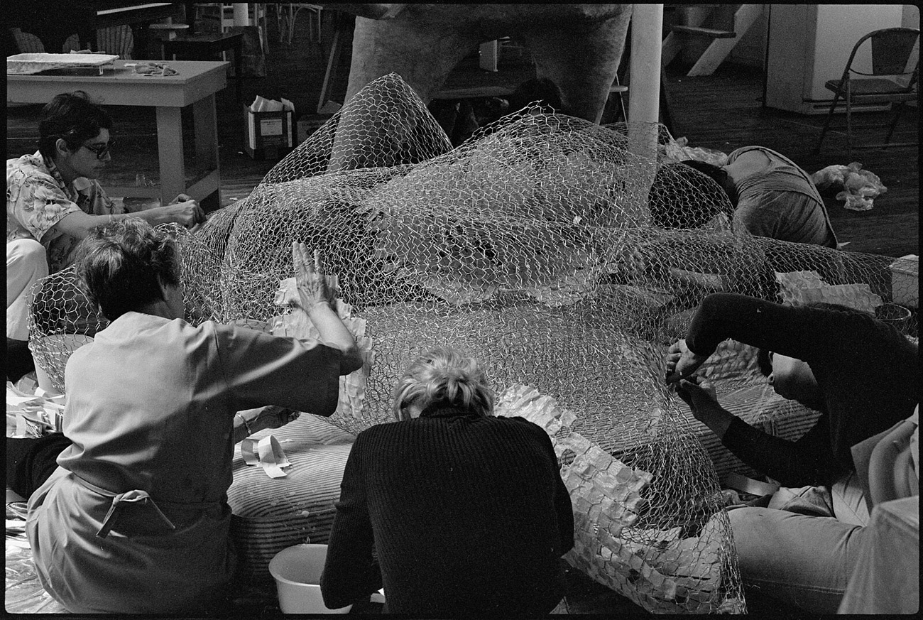 Five people work with large section of wire mesh