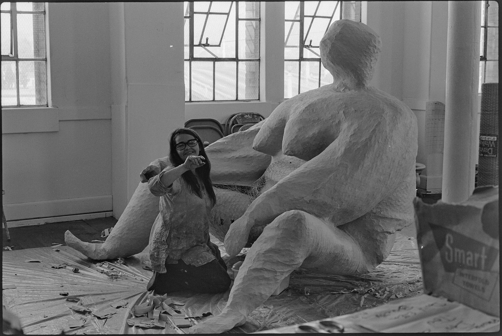 Millett kneels on tarp between legs of large sculpture of nude female figure